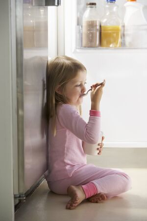 guilty pleasure: Girl Raiding The Fridge Stock Photo