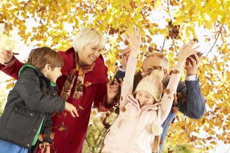 abuelos: Abuelos y nietos con las hojas en otoño Jardín Foto de archivo
