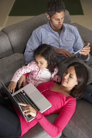 Hispanic Family On Sofa Using Laptop And Digital Tablet Stock Photo