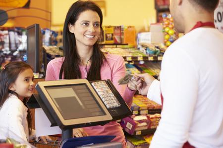 factura: Madre Pagar la familia de compras en la comprobación con la tarjeta Foto de archivo