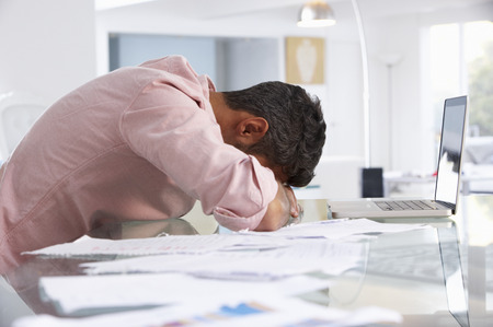 Betonter Mann am Laptop arbeiten in Home Office Standard-Bild