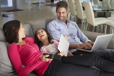 ノート パソコンとデジタル タブレットのテレビを見てソファの上の家族