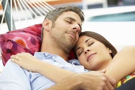 woman resting: Romantic Couple Asleep In Garden Hammock Together Stock Photo