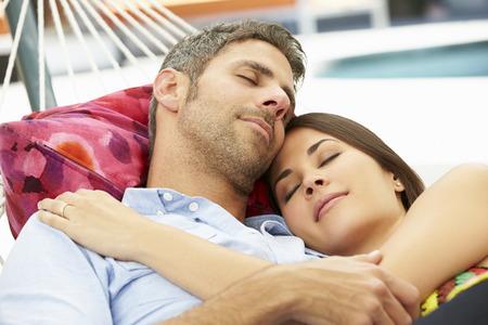 resting: Romantic Couple Asleep In Garden Hammock Together Stock Photo