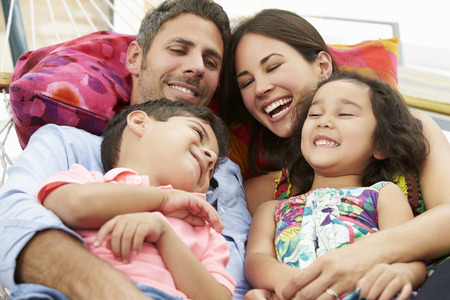 embrace: Family Relaxing In Garden Hammock Together