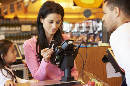 Mother Paying For Family Shopping At Checkout With Card