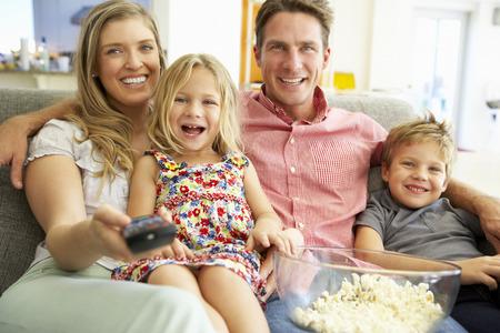 家族一緒にテレビを見ながらソファでリラックス 写真素材