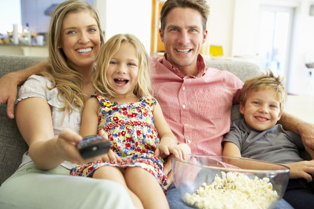 woman watching tv: Family Relaxing On Sofa Watching Television Together Stock Photo