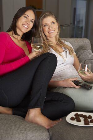 wine drinking: Two Women Sitting On Sofa Watching TV Drinking Wine Stock Photo