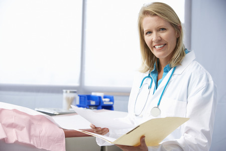 doctor female: Female Doctor In Surgery Reading Patient Notes