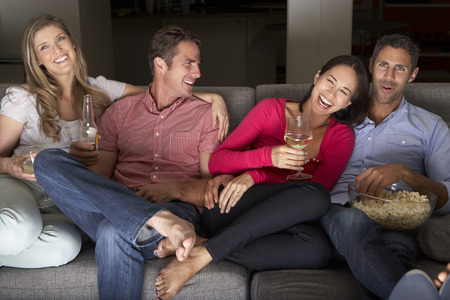 popcorn bowls: Group Of Friends Sitting On Sofa Watching TV Together