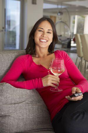 comedic: Hispanic Woman On Sofa Watching TV Drinking Wine