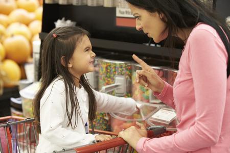 여자 슈퍼마켓에서 사탕 카운터에서 어머니와 함께 인수를 갖는
