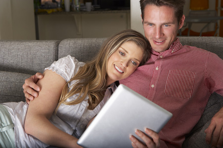 vetical: Couple Sitting On Sofa Looking At Digital Tablet
