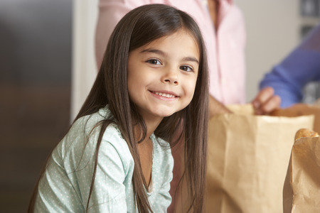 old girl: Family Unpacking Grocery Shopping In Kitchen Stock Photo