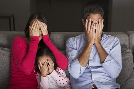 fear woman: Frightened Hispanic Family Sitting On Sofa And Watching TV Stock Photo