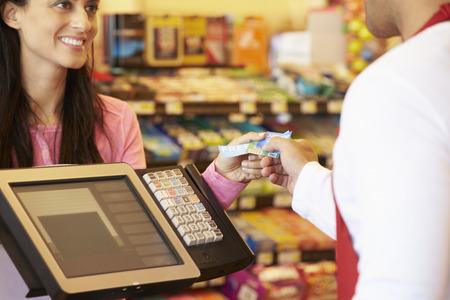 maquina registradora: Cliente que paga por hacer compras en pago con tarjeta