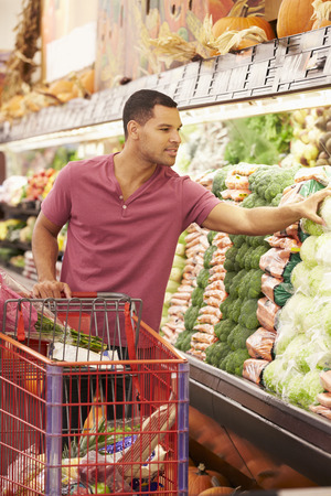 american food: Man Pushing Trolley By Produce Counter In Supermarket
