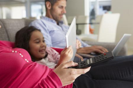 mujer viendo tv: Familia en el sofá con el portátil y la tableta digital Ver la TV Foto de archivo