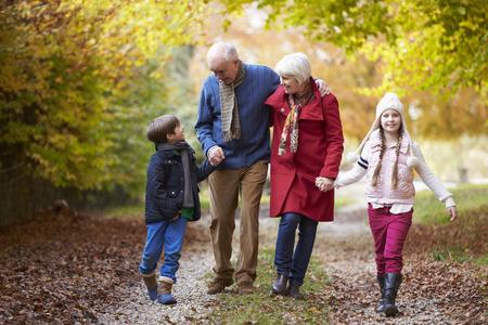 Abuelos con nietos caminando por el camino de otoño