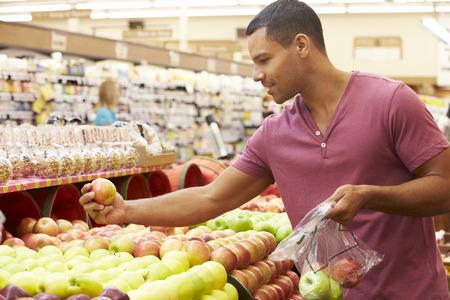 슈퍼마켓에서 과일 카운터에서 남자 스톡 콘텐츠