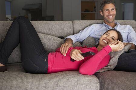 couple relaxing: Hispanic Couple On Sofa Watching TV
