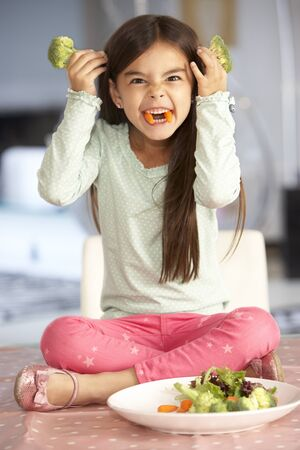 fussy: Girl Making Devil Face With Plate Of Fresh Vegetables