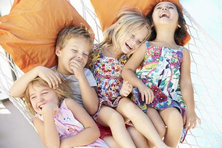 niños riendose: Cuatro niños se relajan en jardín Hamaca Juntos Foto de archivo
