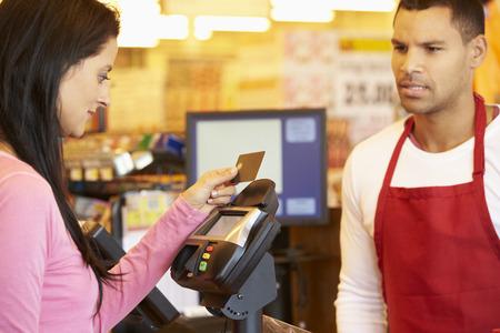 pagando: Cliente que paga por hacer compras en pago con tarjeta