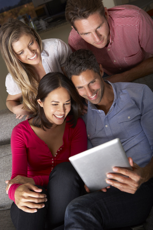 Group Of Friends Sitting On Sofa Looking At Digital Tablet