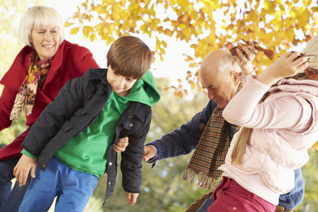 7 year old girl: Grandparents And Grandchildren With Leaves In Autumn Garden
