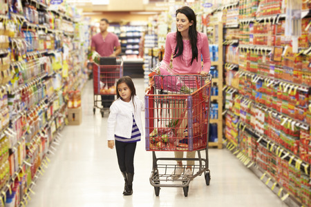 supermarket trolley: Mother And Daughter Walking Down Grocery Aisle In Supermarket