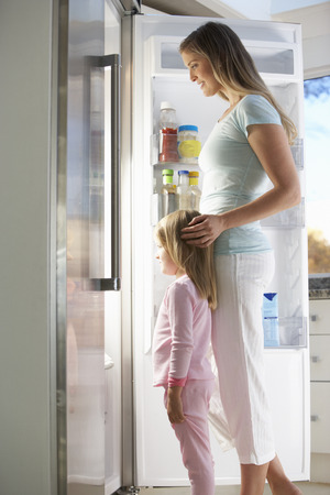 guilty pleasure: Mother And Daughter Choosing Snack From Fridge Stock Photo