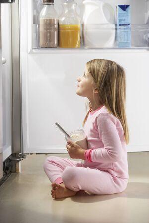 vertical fridge: Girl Raiding The Fridge Stock Photo