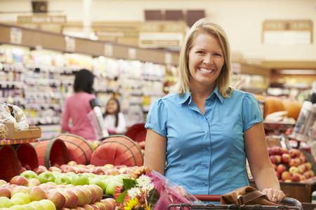 supermercado: Mujer que empuja la carretilla Por Contador fruta en supermercado