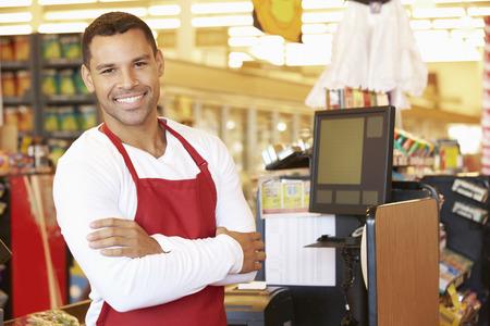 Male Cashier At Supermarket Checkout Banque d'images
