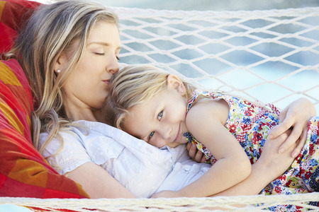 hammock: Mother And Daughter Relaxing In Garden Hammock Together Stock Photo