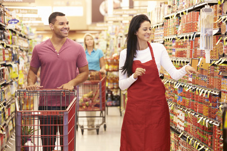woman shopping cart: Man In Grocery Aisle Of Supermarket With Sales Assistant