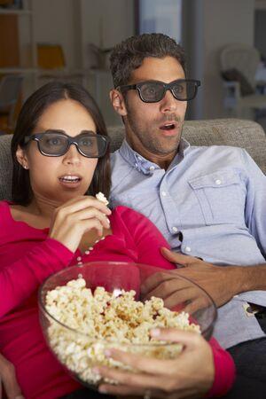 pareja viendo television: Pareja en el sofá que ve la TV El uso de gafas 3D que come las palomitas Foto de archivo