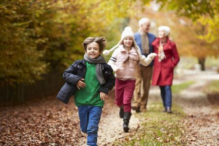 7 year old girl: Grandparents With Grandchildren Running Along Autumn Path