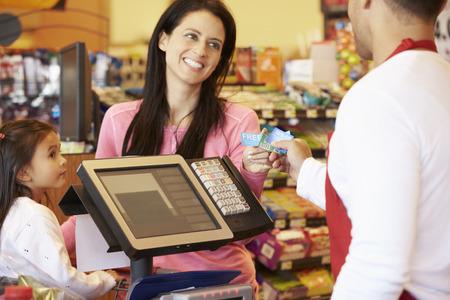 pagando: Madre Pagar la familia de compras en la comprobación con la tarjeta Foto de archivo