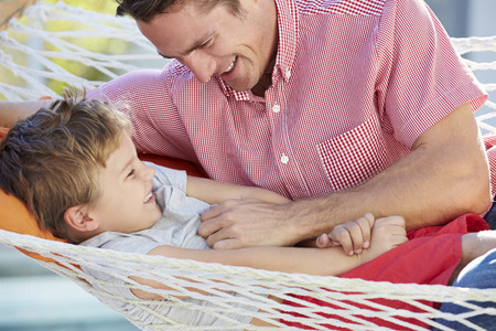tickling: Father And Son Relaxing In Garden Hammock Together