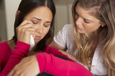 femme triste: Femme assise sur le canapé Réconfortant malheureux ami