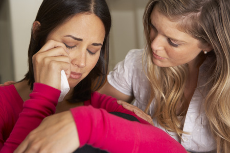 sad people: Woman Sitting On Sofa Comforting Unhappy Friend