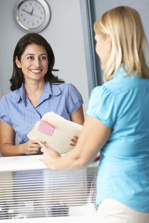 recepcion: Paciente de sexo femenino con Recepcionista en los doctores Sala de espera
