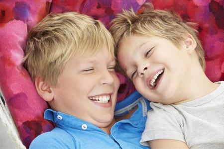niños riendose: Dos Young Boys que se relajan en jardín Hamaca Juntos