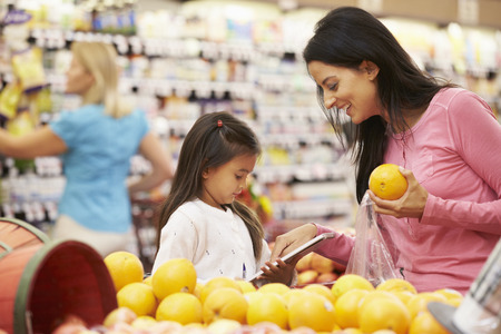 Mother And Daughter At Fruit Counter In Supermarket With List Zdjęcie Seryjne - 42271164