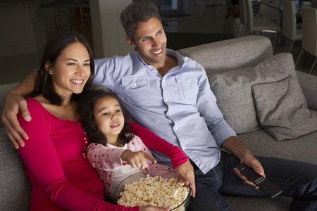 Hispánský dívka sedí na pohovce a sledování televize s rodiči Reklamní fotografie