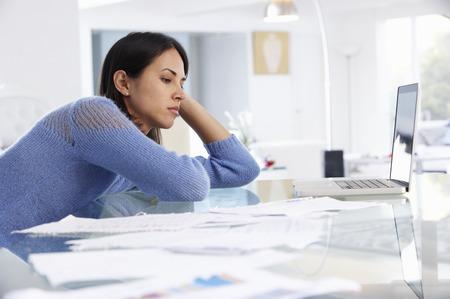 ホーム オフィスのラップトップで働く女を強調しました。