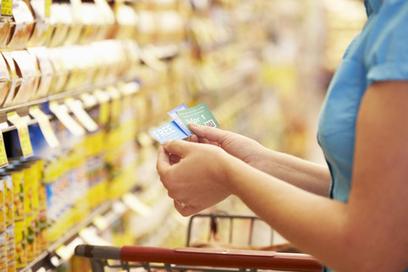food shelf: Woman In Grocery Aisle Of Supermarket With Coupons
